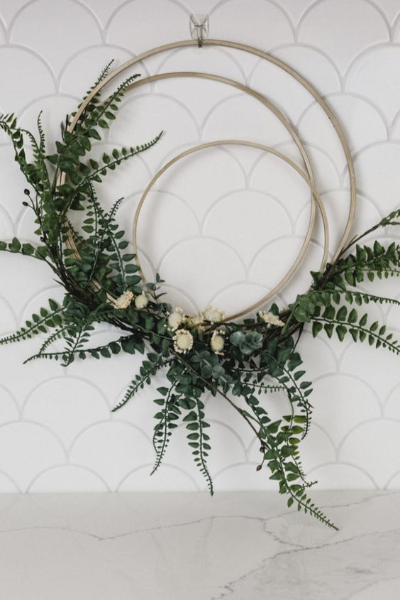 a modern wreath of several hoops, greenery and white blooms is a very fresh and new idea for spring