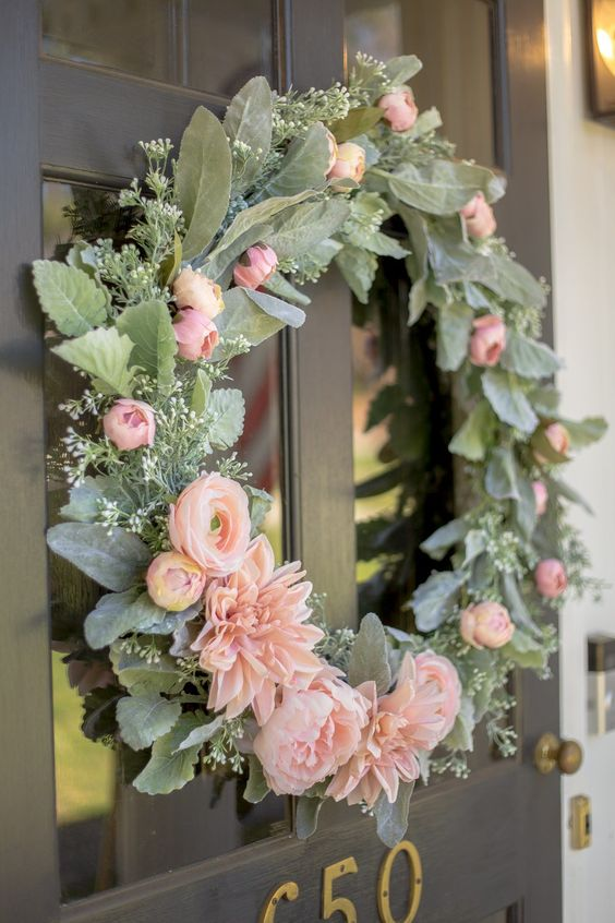 a pretty and cool spring wreath with pale greenery, pink blooms and foliage is a very beautiful idea for your front door
