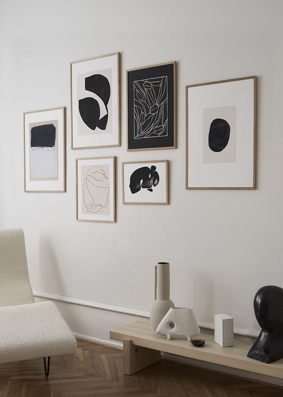 a minimalist gallery wall with a free form and matching stained frames of various sizes is a cool idea for a modern space