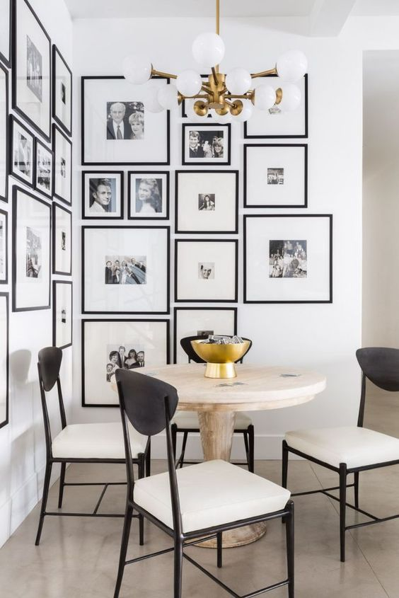 a modern and elegant free form gallery wall covering a whole corner and with matching black frames and white mats is wow
