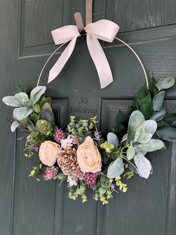a pretty modern spring wreath with greenery, pink and blush blooms and a blush ribbon bow on top is a lovely idea