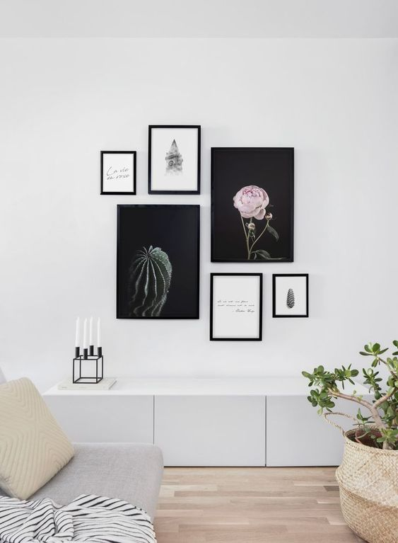 a modern free form gallery wall with mismatching frames and no frame art, with beautiful artsy posters