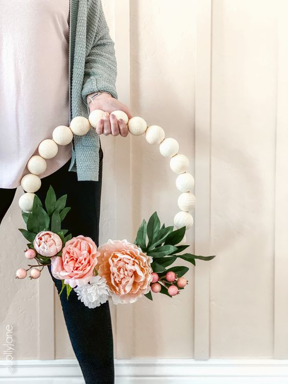 a pretty spring wreath of large wooden beads, pink blooms and berries and faux leaves is a simple and long-lasting decoration