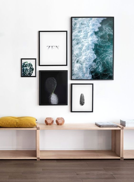 a modern free form gallery wall with mismatching frames and ultra-modern artworks and prints looks fresh and bold