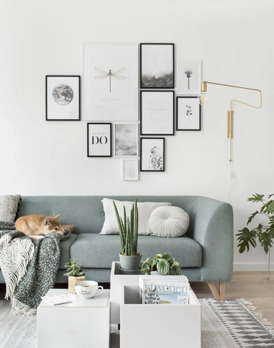 a pretty modern gallery wall with mismatching black and white frames and a free form looks fresh thanks to the artworks chosen