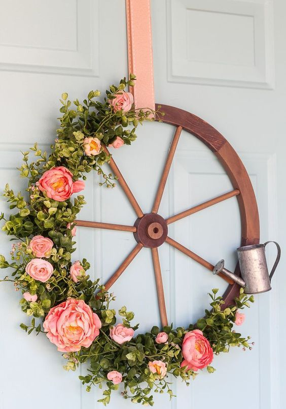 a rustic spring wreath of a large wooden wheel, artificial greenery and pink peonies and a little watering can is very cool