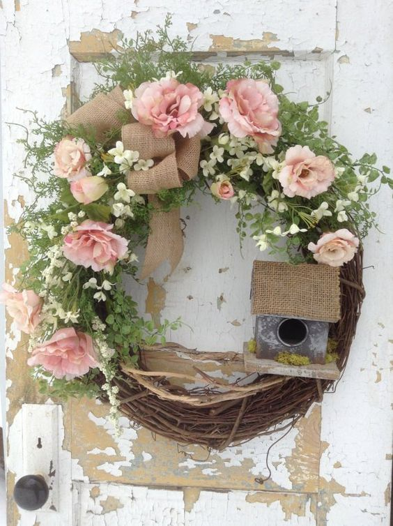 a rustic spring wreath of vine, greenery, white and pink blooms, a mini bird house and some moss