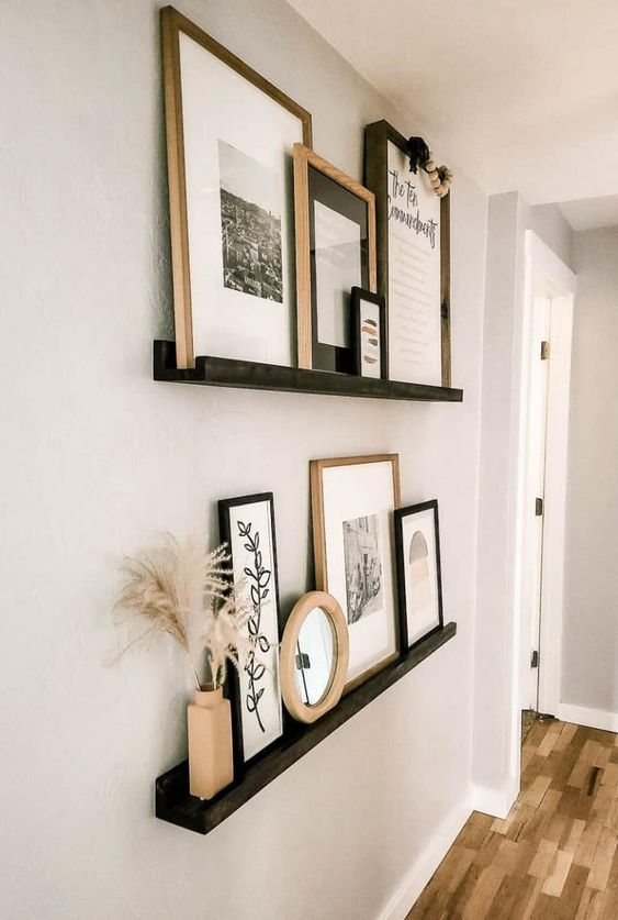 black ledges with black and white artworks and prints placed in light stained and black frames, a clock and a terracotta vase