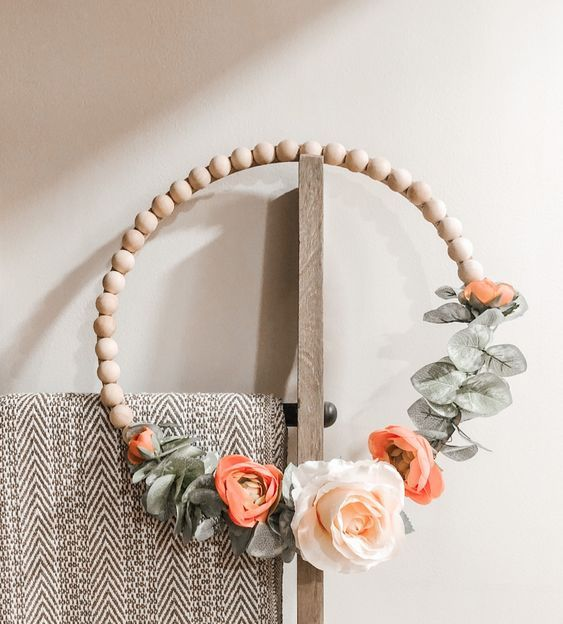 a spring wreath of wooden beads, with faux foliage and orange and white blooms is a modern idea for a front door