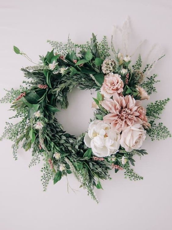 a stylish spring wreath of lots of textural greenery, white and pink blooms is a very fresh idea