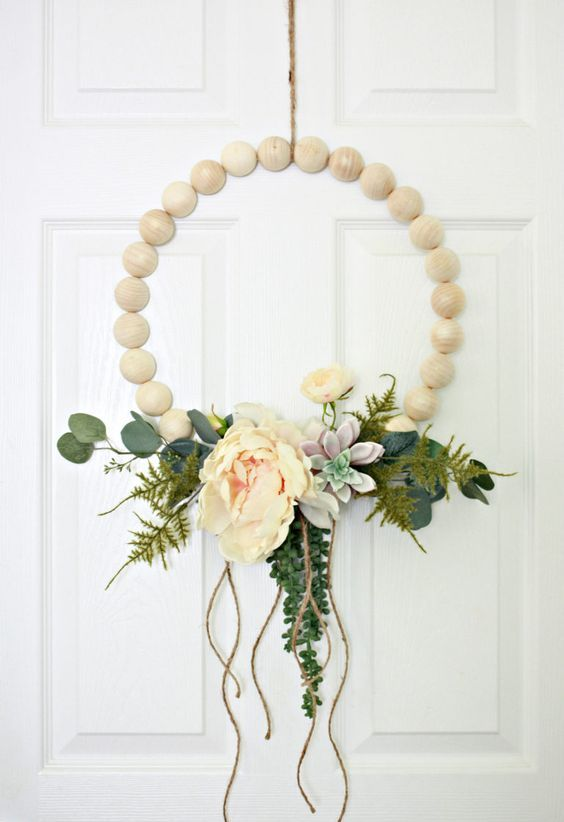 a wooden ball hoop wreath with artificial greenery, succulents, peachy blooms and some twine hanging down