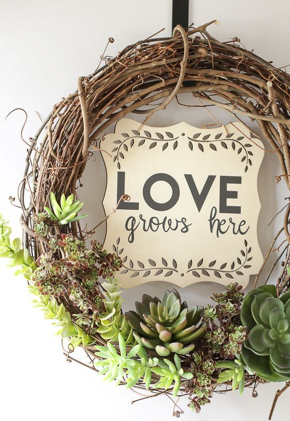 an awesome spring wreath of vine and succulents plus a plywood plaque is a cool and very modern idea