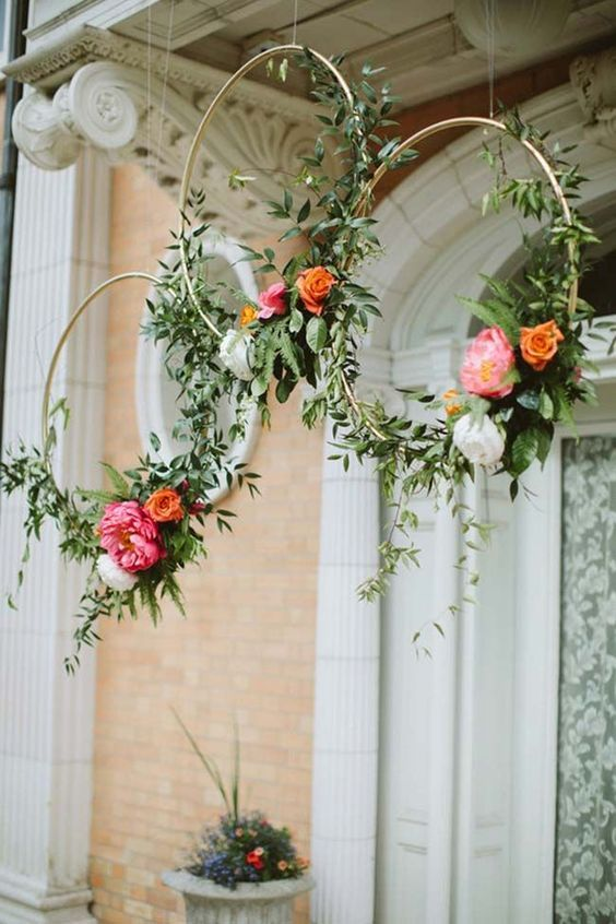 hanging spring wreaths of gold hoops, greenery and bold blooms are great to turn your porch into a spring space