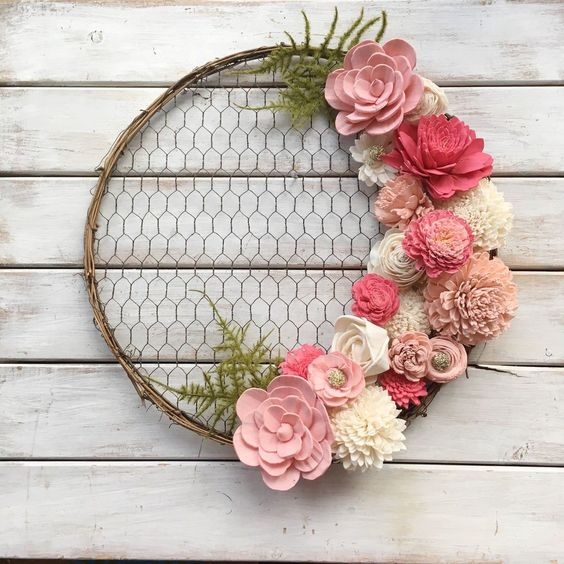 a simple rustic spring wreath of chicken wire, vine, pink faux blooms and fabric ones plus greenery