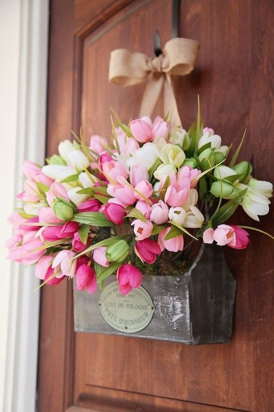 a substitute to a spring door wreath - a box with moss, pink and white tulips and a burlap bow looks creative and feels rustic