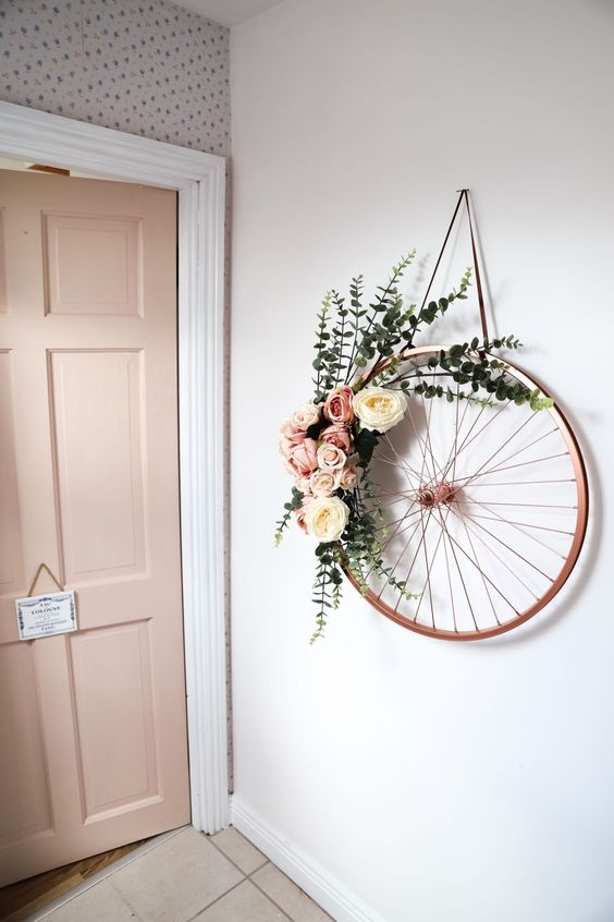 an old bike wheel wreath with pink and white blooms plus eucalyptus is a beautiful and rustic idea for spring