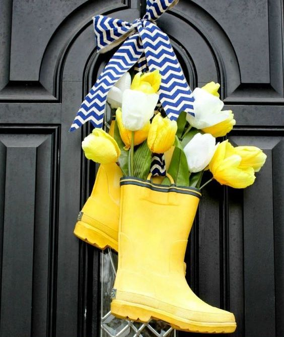 bright yellow rain boot decor with yellow and white tulips and a chevron bow is a very cool and bold idea