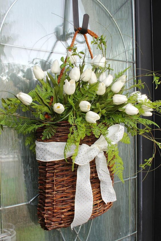 a basket with ferns, white tulips, a polka dot ribbon bow is a lovely alternative to a usual spring wreath