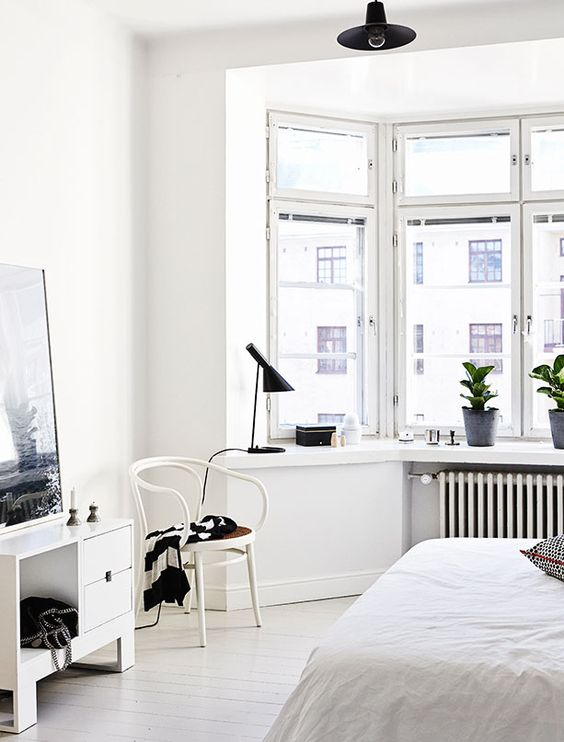 a Nordic bedroom in white, with a bow window and much light, plus touches of black for more drama
