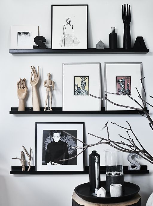 a Nordic gallery wall with black ledges contrasting the white wall, bold art, statuettes and monograms plus branches