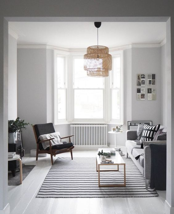 a Nordic living room with a monochromatic color scheme, graphic pillows, a bow window and a woven pendant lamp