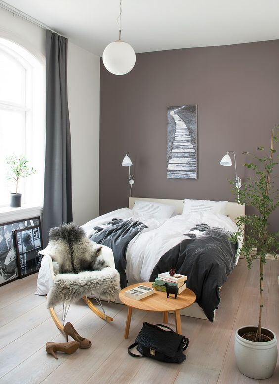 a Scandinavian bedroom with a mauve accent wall, a creamy bed, a chair and a table, sconces and some potted greenery