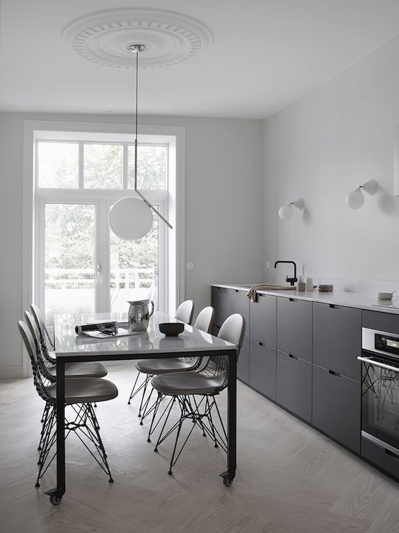a Scandinavian black one wall kitchen with a white coutnertop and black fixtures plus some sconces and a pendant lamp