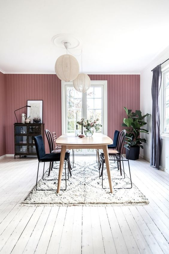 a Scandinavian dining room with a mauve wall, a wooden table, mismatching chairs, paper lamps and a dark buffet