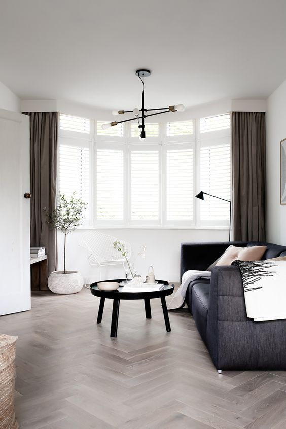 a Scandinavian living room with a bow window, a black sofa, a round table and taupe curtains paired with shutters