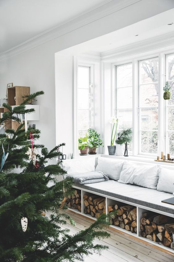 a Scandinavian space with a bow window and a windowsill bench with firewood storage, potted plants and much natural light