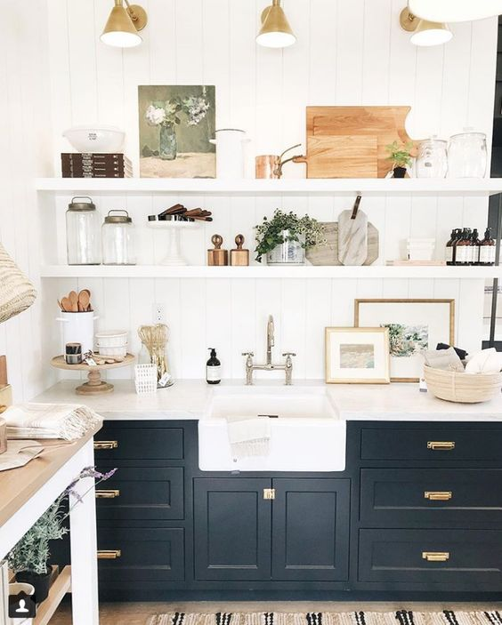 a beautiful black farmhouse kitchen with shaker cabinets, floating shelves, retro sconces and mixed metals for more eye-catchiness