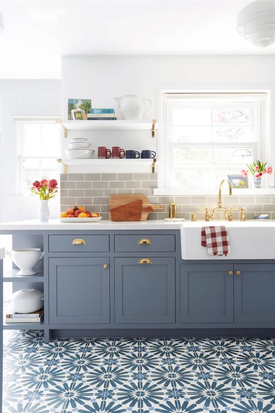a beautiful blue shaker style kitchen with a grey subway tile backsplash, white quartz countertops and touches of brass