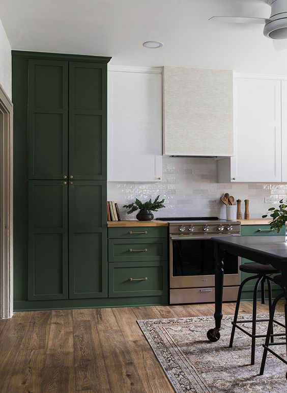 a beautiful dark green and white kitchen in vintage style, with a neutral hood and butcherblock countertops is chic