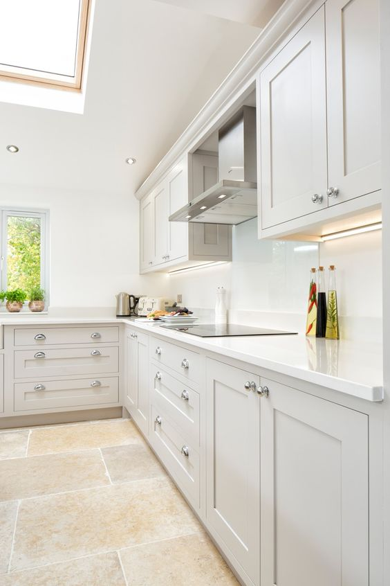 a beautiful dove grey shaker style kitchen with white countertops and a backsplash, stainless steel touches and built-in lights