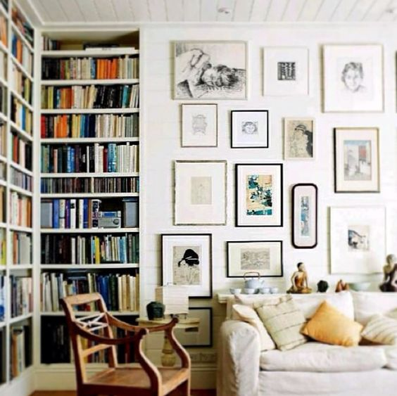 a beautiful free form gallery wall with thin black and silver frames and black and white and colored art