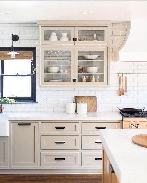 a beautiful light stained shaker style kitchen with a white subway tile backsplash and white quartz countertops plus black fixtures
