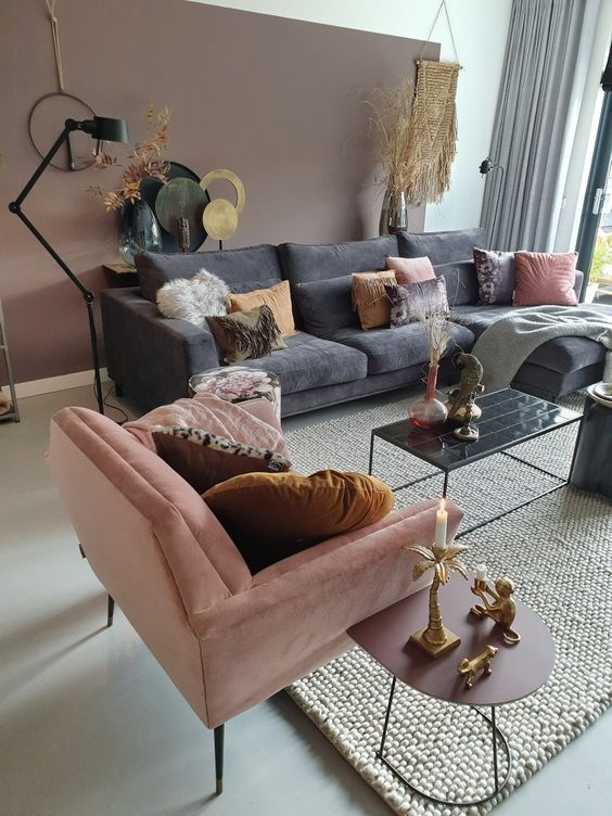 a beautiful living room with a mauve accent wall, grey and pink furniture, touches of black and gold is cool