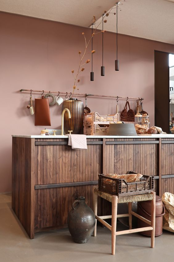 a beautiful mauve kitchen with a large wood clad kitchen island, pendant lamps, stools and various vases and buckets