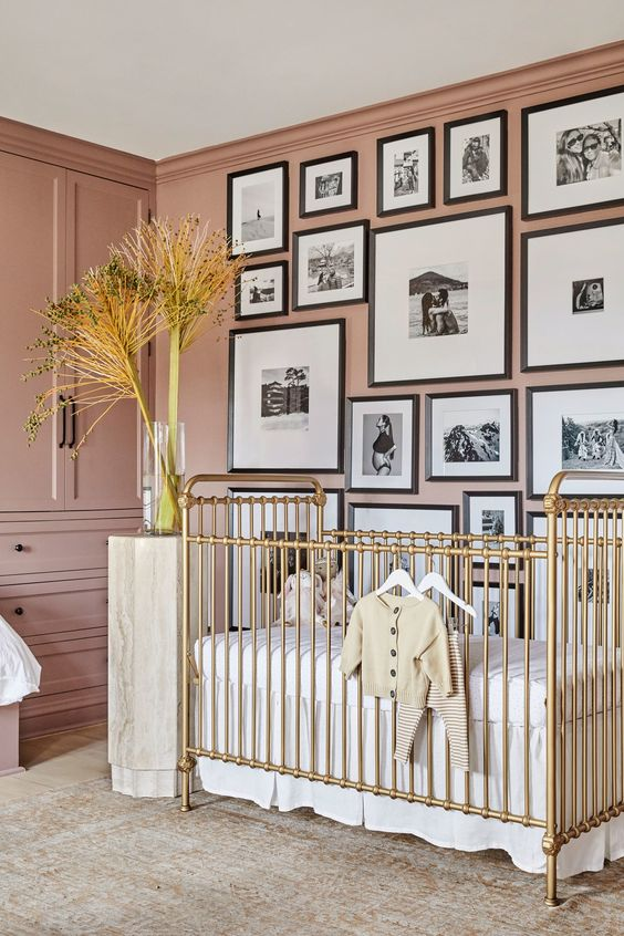 a beautiful mauve nursery with built-in furniture, a gold crib, a monochromatic gallery wall and neutral textiles