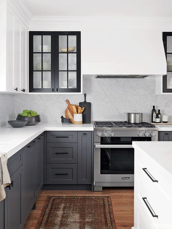 a beautiful two tone kitchen with grey and white shaker style cabinets, white quartz countertops and a backsplash plus a boho rug