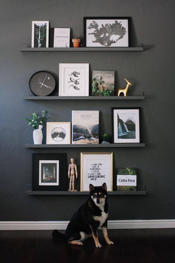 a black wall with black ledges and chic artworks, books, statuettes of various kinds, a clock and some potted greenery