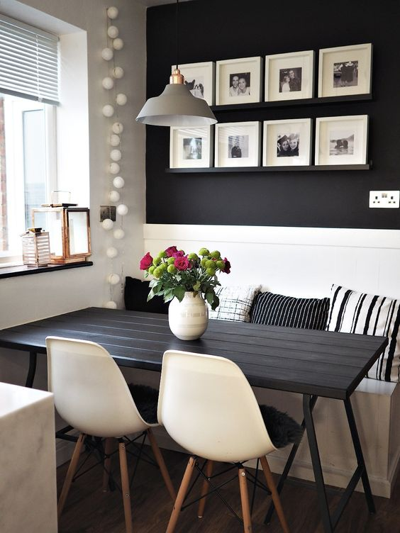 a black wall with black ledges that are almost invisible and black and white photos in white frames form a grid gallery wall