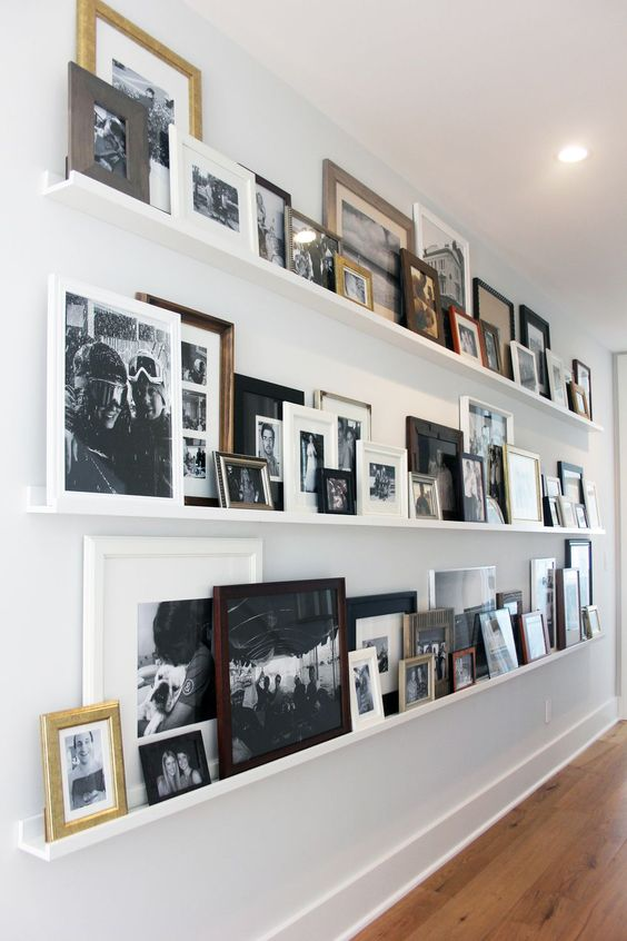 a blank wall int he corridor taken by long white ledges and all kinds of family photos in black and white in mismatching frames adds warmth and coziness to the house
