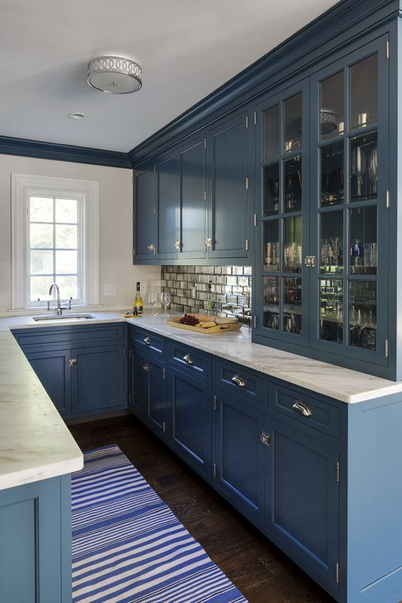 a blue U-shaped kitchen with white stone countertops and a mirror tile backsplash is a very stylish space