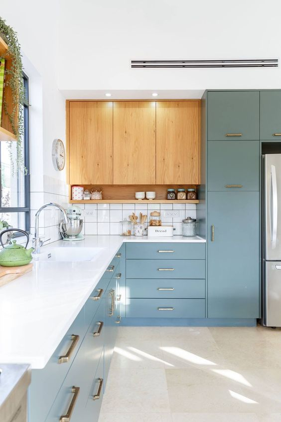 a blue and light-stained kitchen with a white countertop plus a white tile backsplash and gold and brass handles