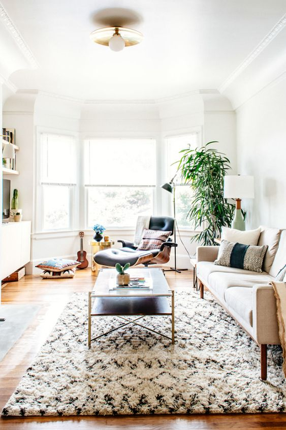 a boho lux living room with a bow window, a comfy lounger next to it, a neutral sofa and a low coffee table plus potted plants