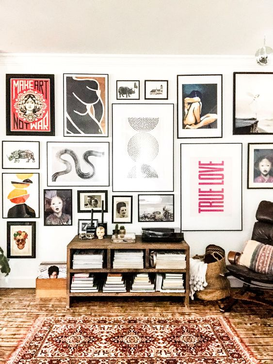 a bold and eye-catchy gallery wall with various types of art in mismatching black frames will make a statement anywhere