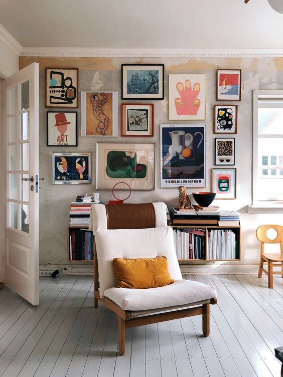 a bold and jaw-dropping gallery wall with lots of abstract art in mismatching frames gives a character to this neutral space