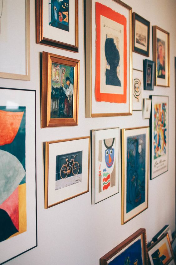 a bold gallery wall with a free shape, mismatching frames and colorful paintings, prints and posters with a vintage feel