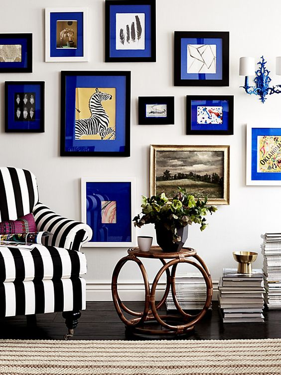 a bold gallery wall with black and white frames and electric blue mats for a more cohesive and a bit crazy look